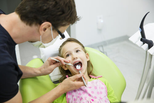 Dentist working on little girl