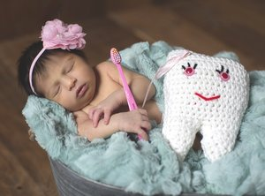 Baby sleeping with toothbrush and tooth pillow