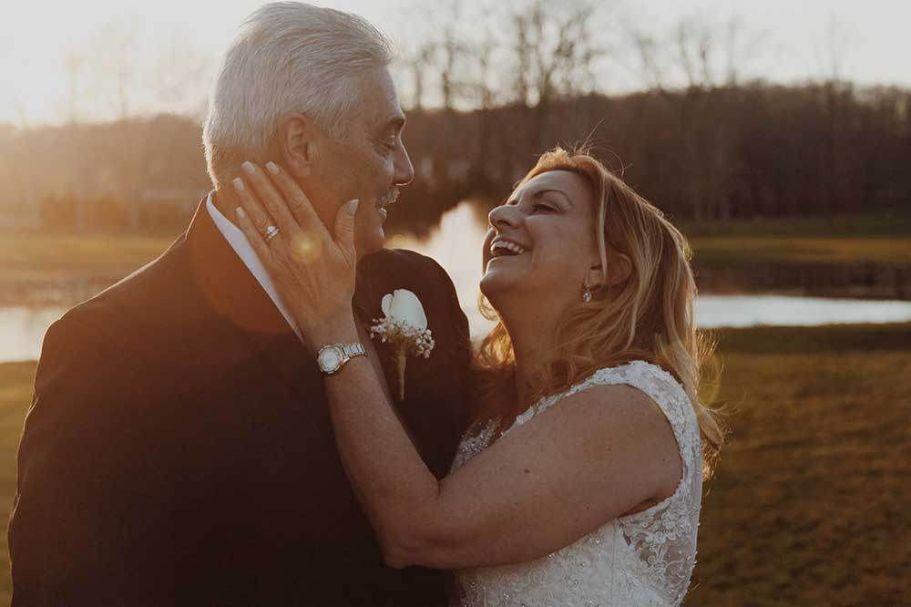 Older couple at a wedding, smiling and looking at each other