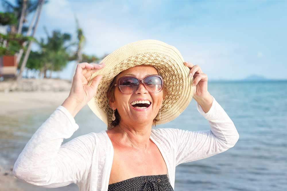 A smiling older woman on the beach wearing a straw had and sunglases